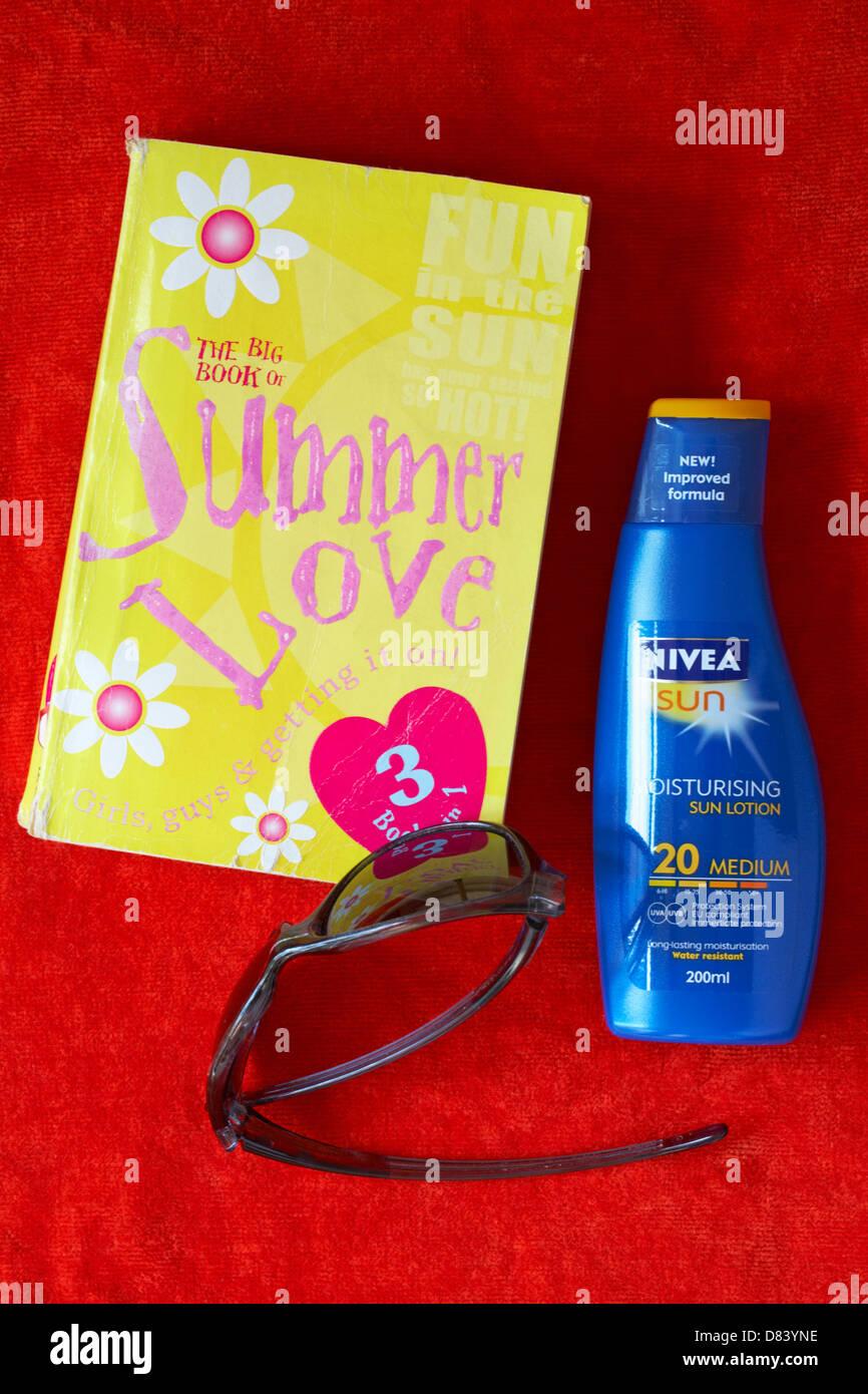 The big book of Summer Love book, sunglasses and Nivea Sun suntan lotion on orange towel - concept of holiday romance - Stock Image