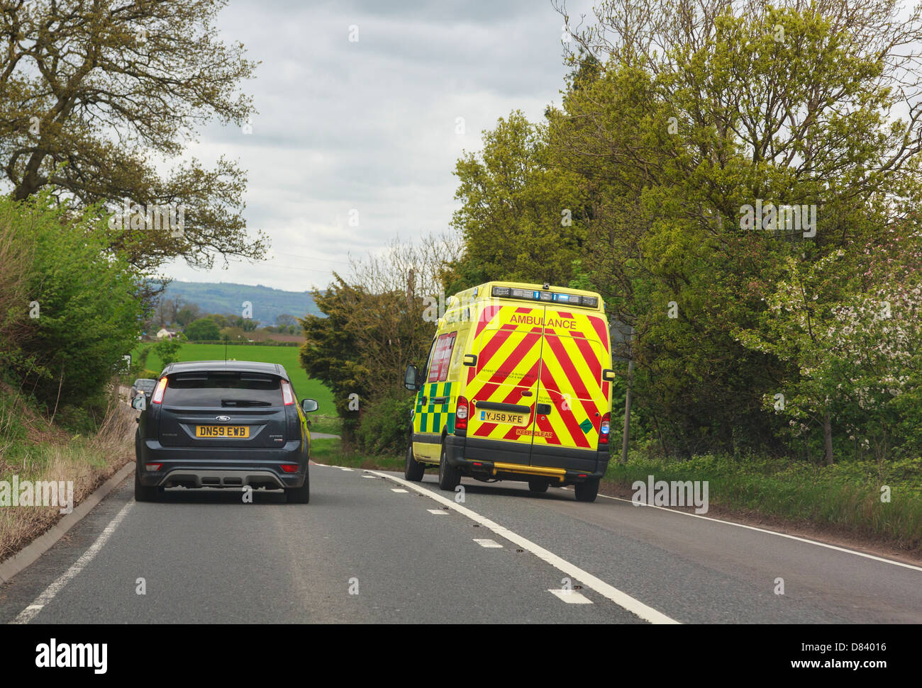 View through a windscreen of an ambulance with blue lights flashing rushing to an emergency overtaking a car along - Stock Image