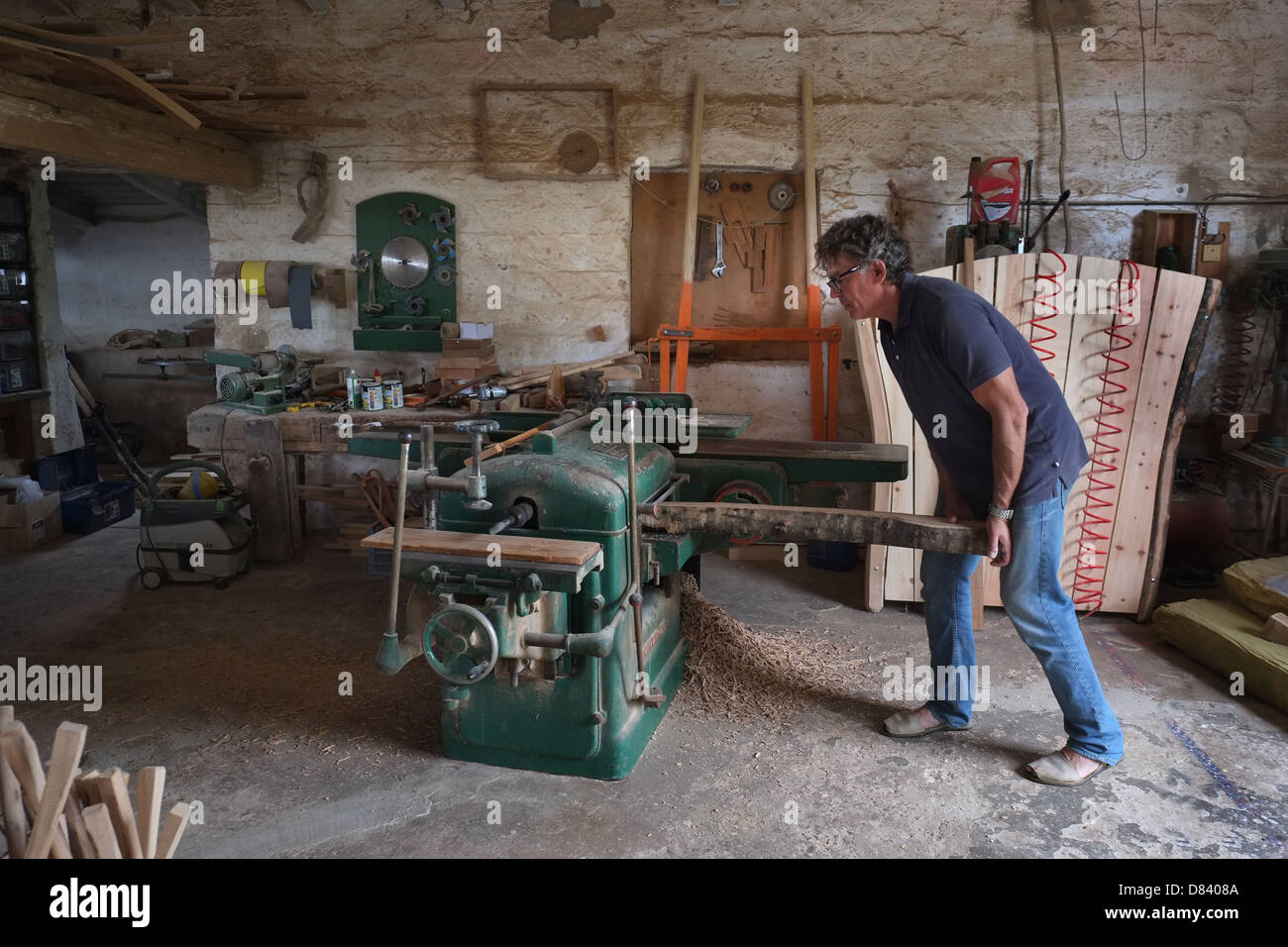 Woodworker, or arader, using planing machine in his workshop, Menorca, Spain - Stock Image