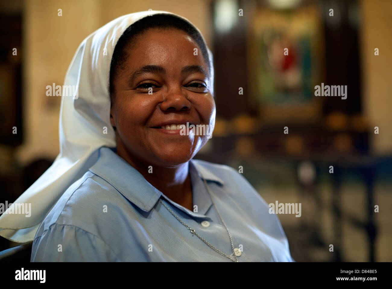Woman and religion, portrait of catholic nun praying in church and looking at camera - Stock Image