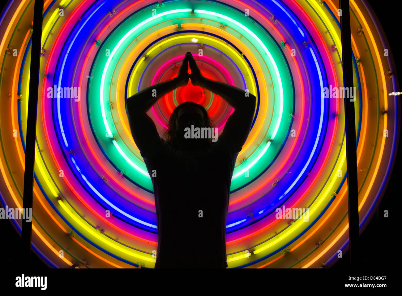 Silhouette of a man in front of neon lights - Stock Image