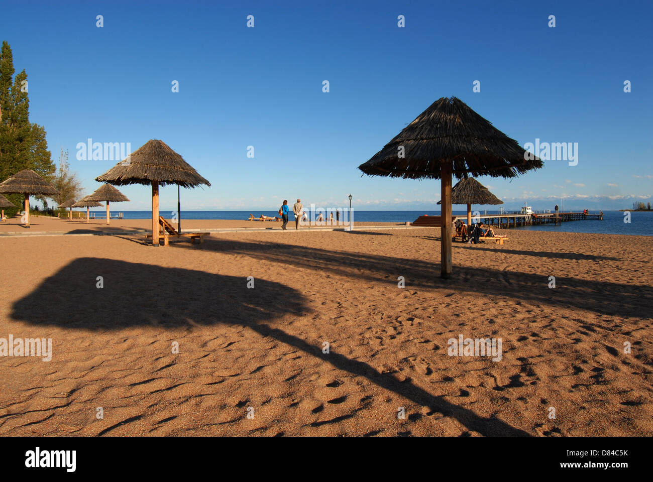 Few shelters at the beach of the Issyk Kul lake an the sunset. Issyk Kul region, Kyrgyzstan - Stock Image