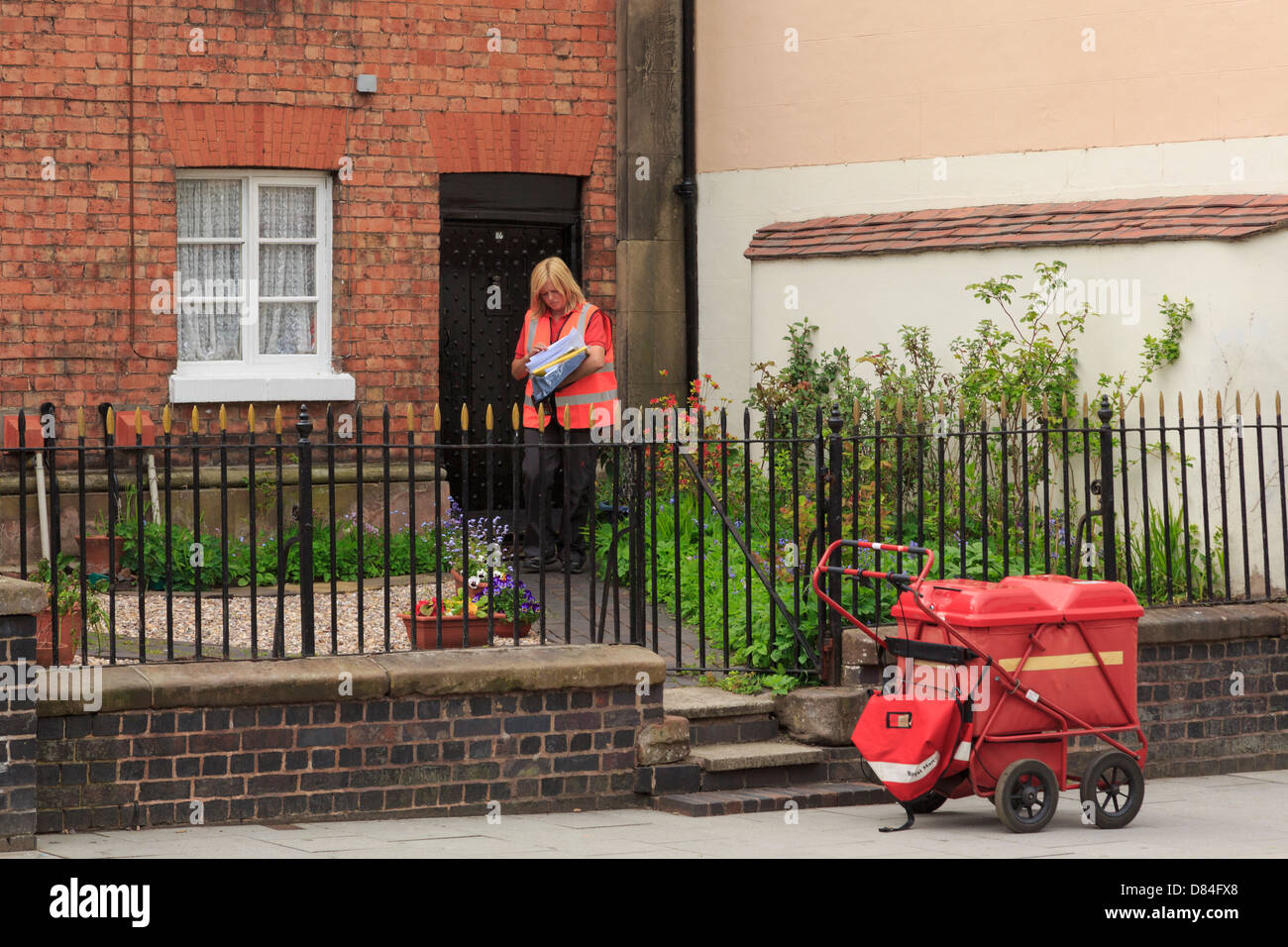 A female Royal Mail postal worker delivering post to a house on her round in Newport, Shropshire, England, UK, Britain - Stock Image