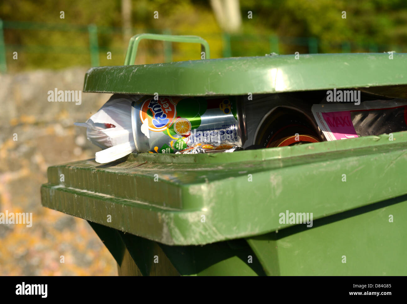 wheelie bin overflowing with rubbish - Stock Image
