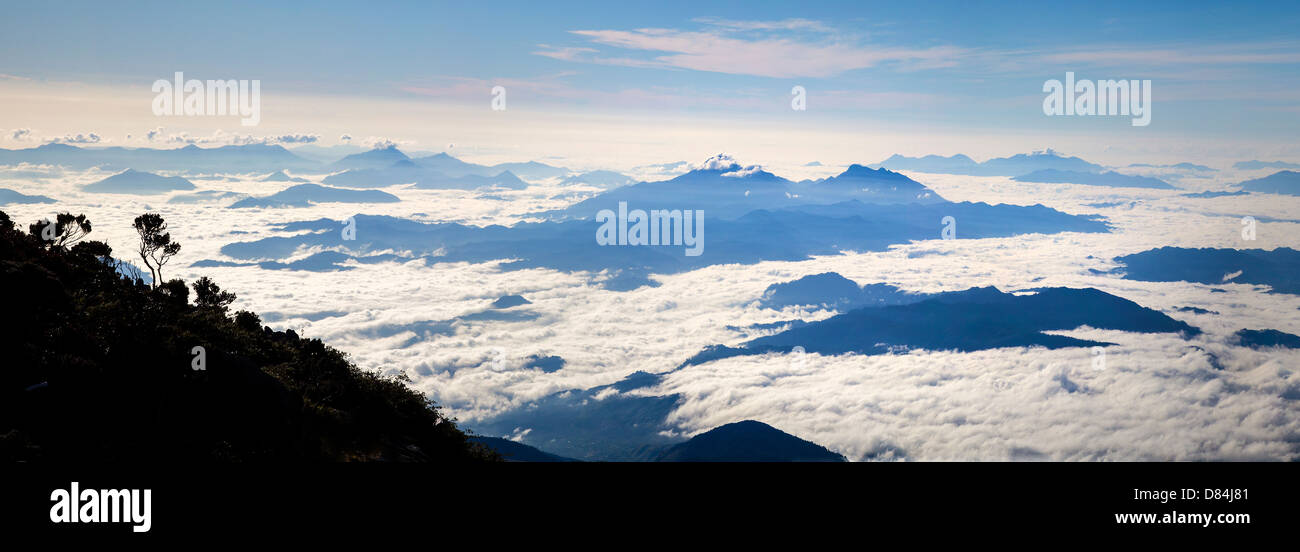 Panoramic view over the cloud fringed foothills of Mount Kinabalu and the Crocker Range from its upper slopes soon - Stock Image