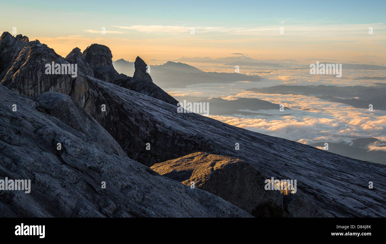 View from the summit of Mount Kinabalu Borneo of the Ugly Sister Peak and clouded landscape beyond - Stock Image
