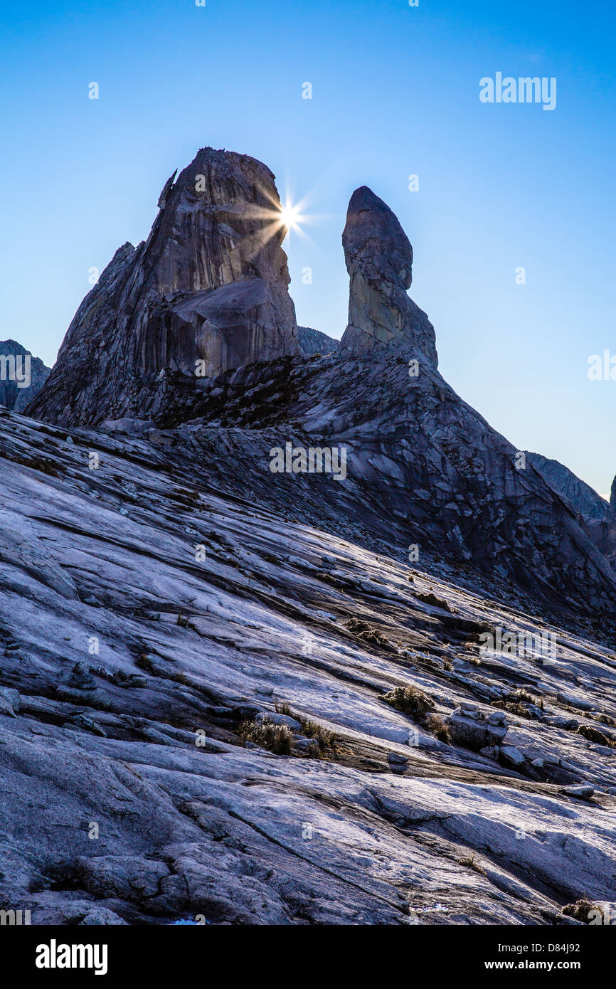 Sunstar emerging from behind the Donkey's Ears Peak near the summit of Mount Kinabalu in Sabah Borneo - Stock Image