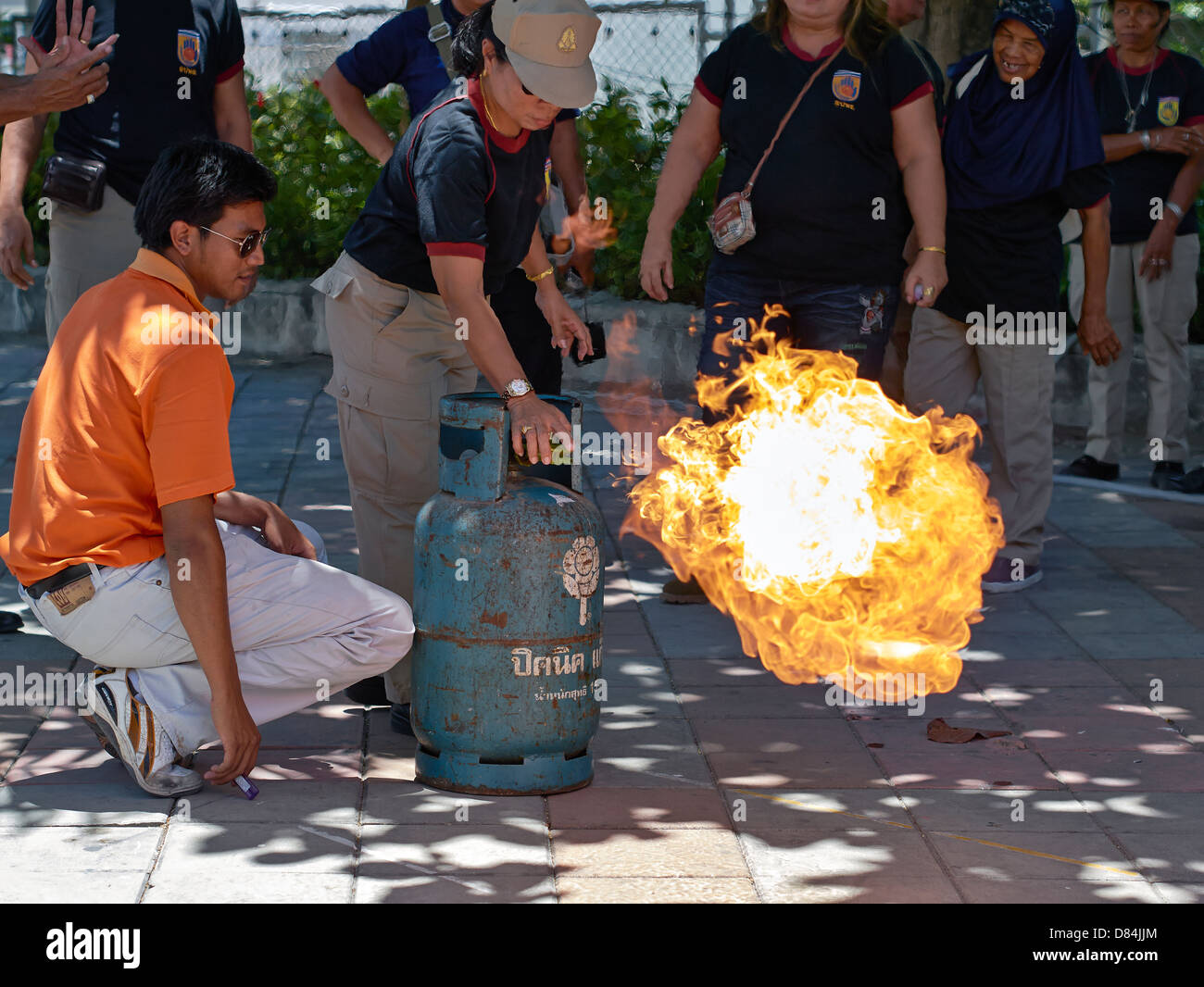 Thailand fire officer demonstrating the safe method to extinguish flame from a propane gas bottle. Home appliance - Stock Image