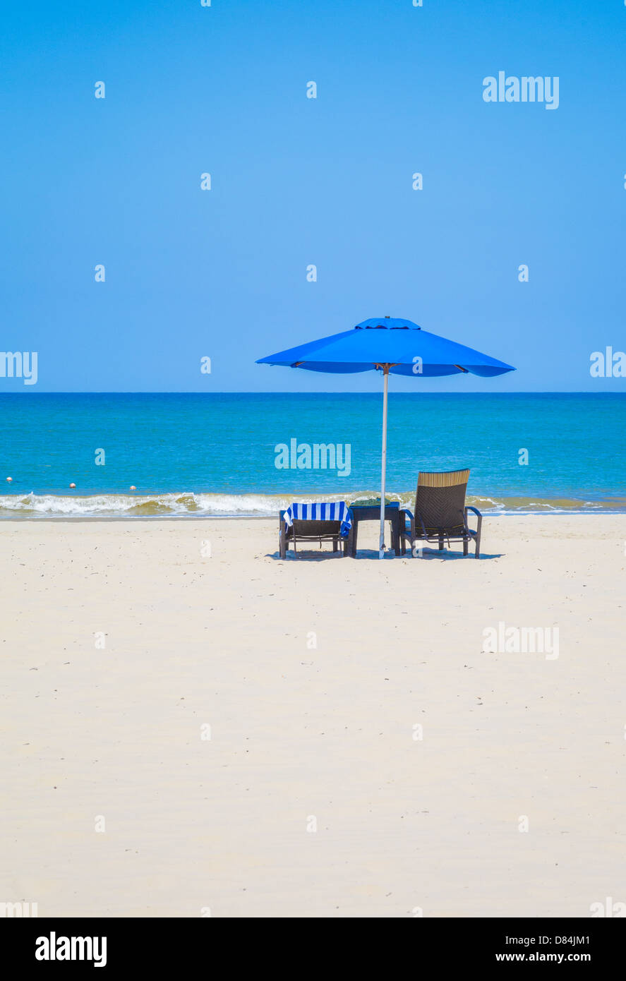 Blue sunshade and two loungers one with a hotel towel on the beach at Rasa Ria in Sabah Borneo - Stock Image