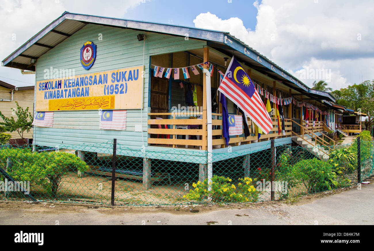 Village school in Sukau by the Kinabatangan River in Sabah Borneo decked with Malaysian and other flags - Stock Image