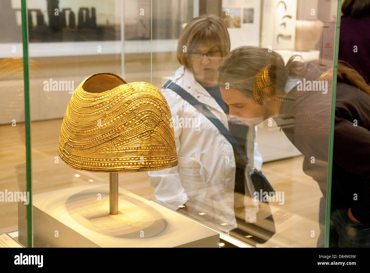 Visitors looking at the Bronze Age Mold Gold Cape exhibit; the British Museum, London UK - Stock Image