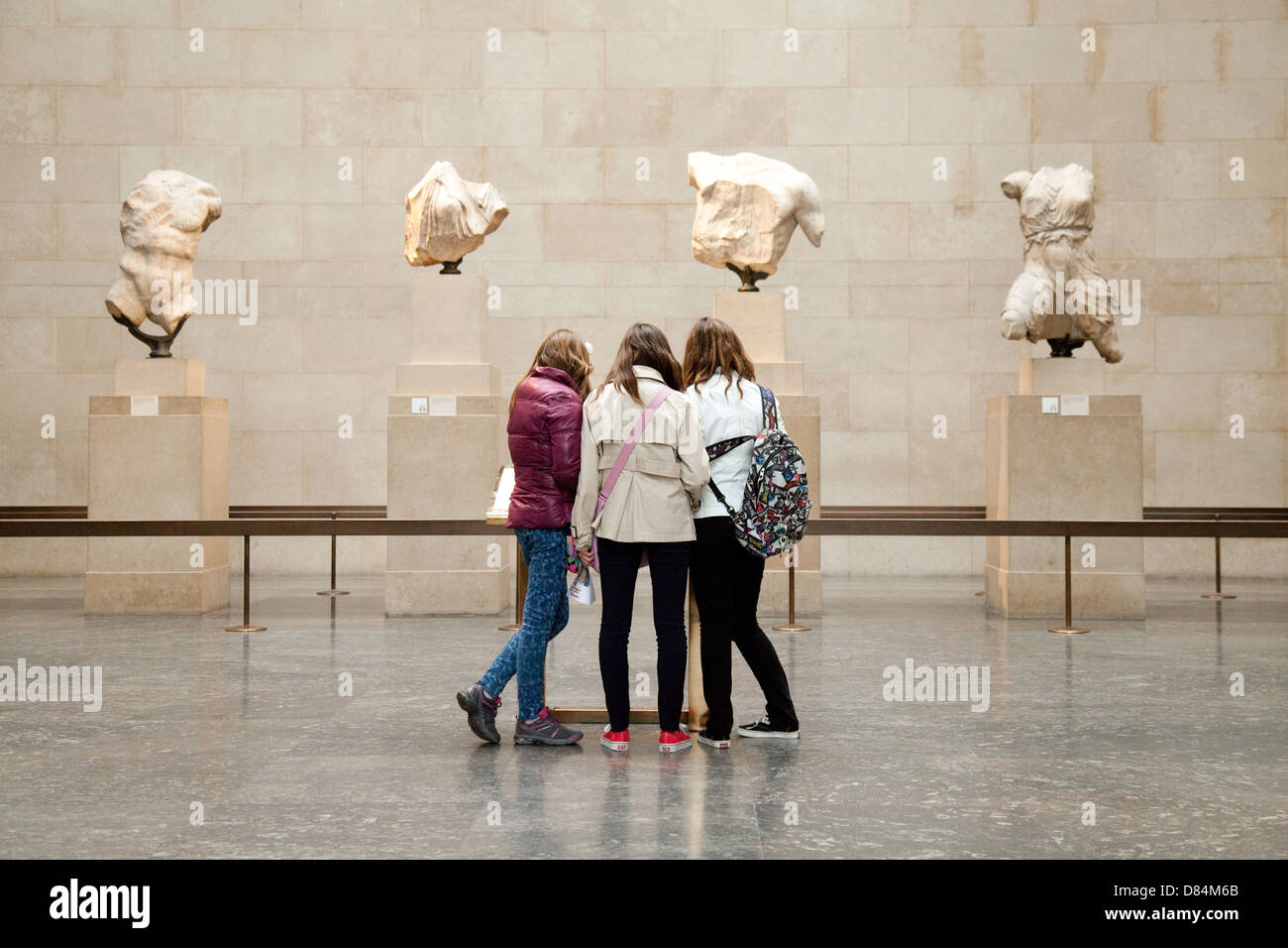 Three teenage girls teenagers looking at the Elgin Marbles, Greek Gallery, British Museum, London UK Stock Photo