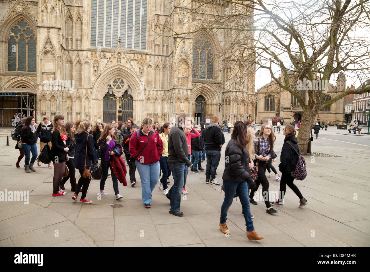 Group of teenagers on a secondary school trip outside York Minster cathedral, Yorkshire, England UK - Stock Image