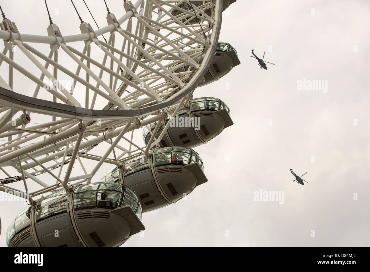 The London Eye, London, UK, with two helicopters flying past. - Stock Image