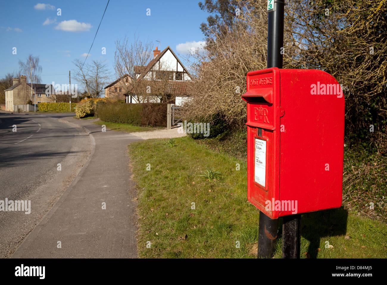 A red Village royal mail postbox mailbox, Swaffham Prior, Cambridgeshire UK - Stock Image