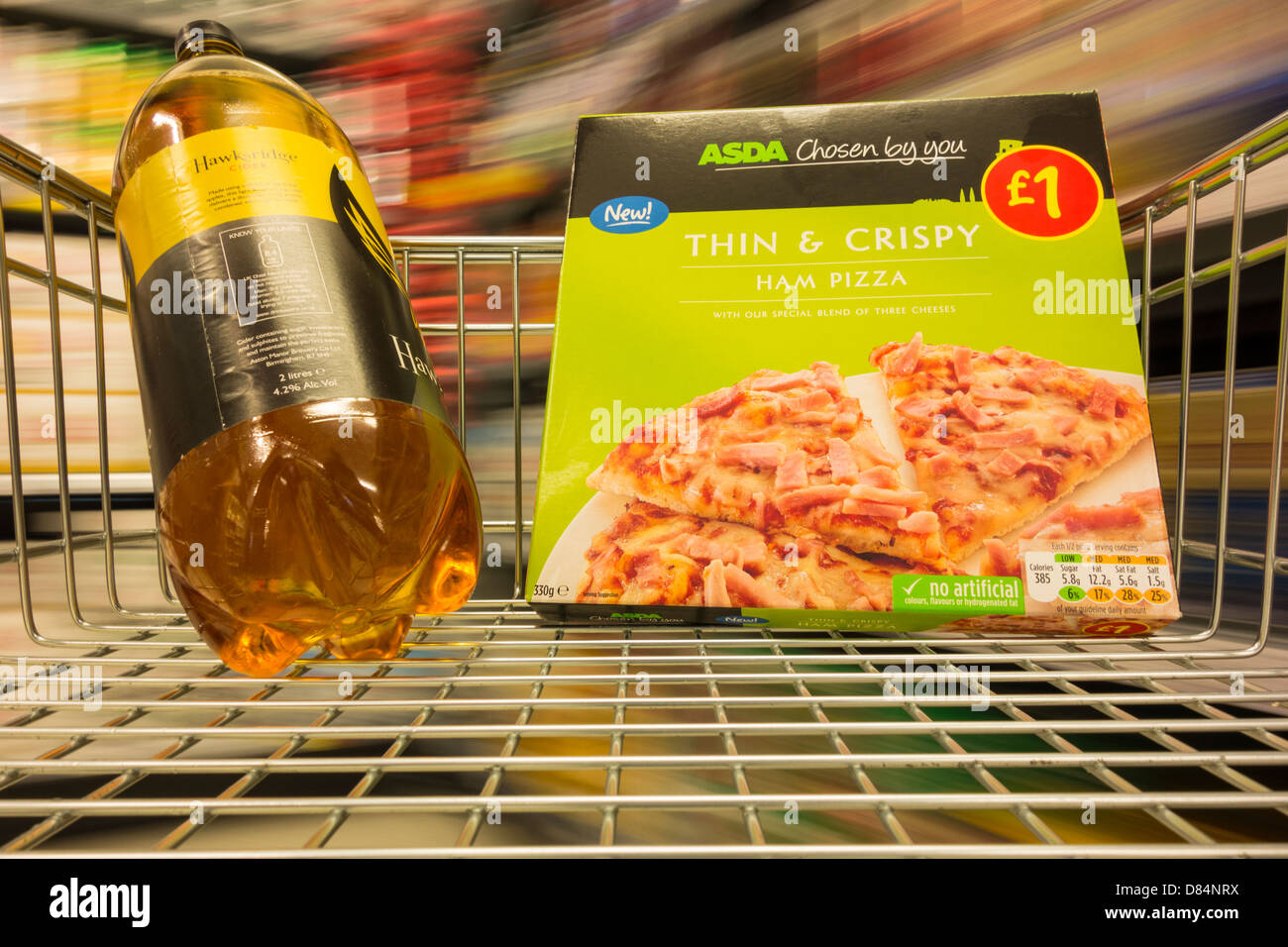Pizza and bottle of Cider in supermarket trolley - Stock Image
