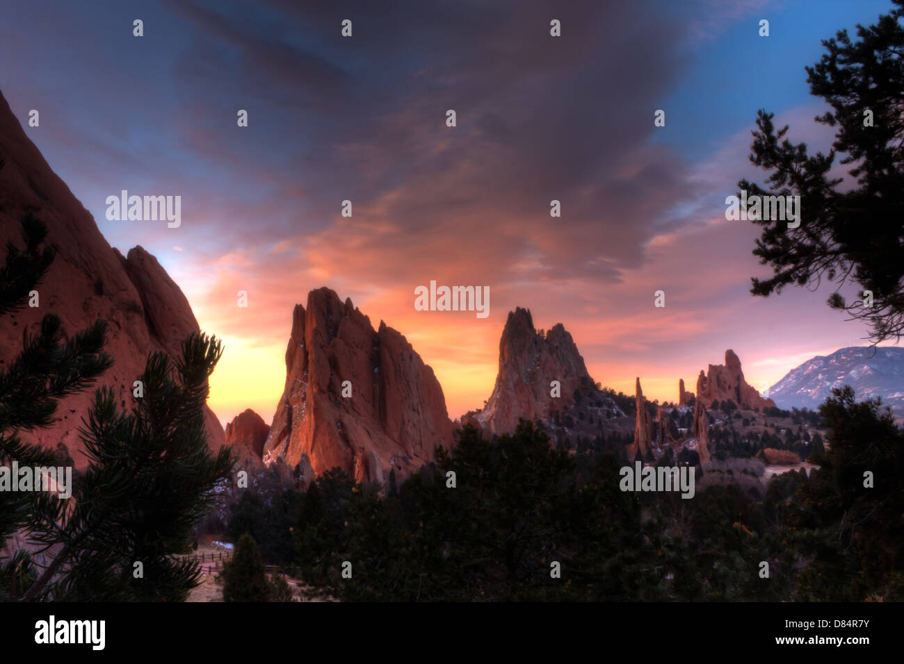 Beautiful HDR image of purple and orange sunrise clouds over red rock formations at Garden of the Gods, Colorado - Stock Image