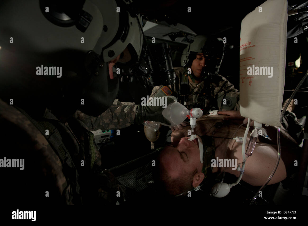 U.S. Army medics simulating ventilation of a mock patient aboard a UH-60 Blackhawk - Stock Image