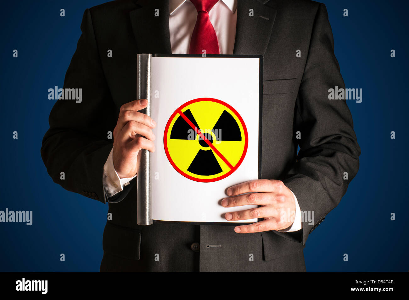 Man in black suite is holding a folder with sign no atomic power - Stock Image