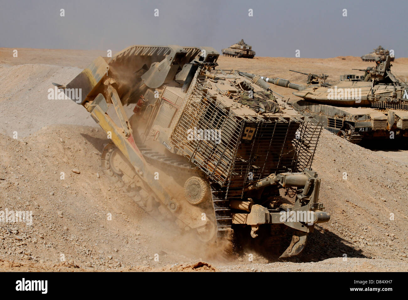 An Israel Defense Force armoured Caterpillar D-9 clearing the way for Mark IV main battle tank during an exercise. - Stock Image