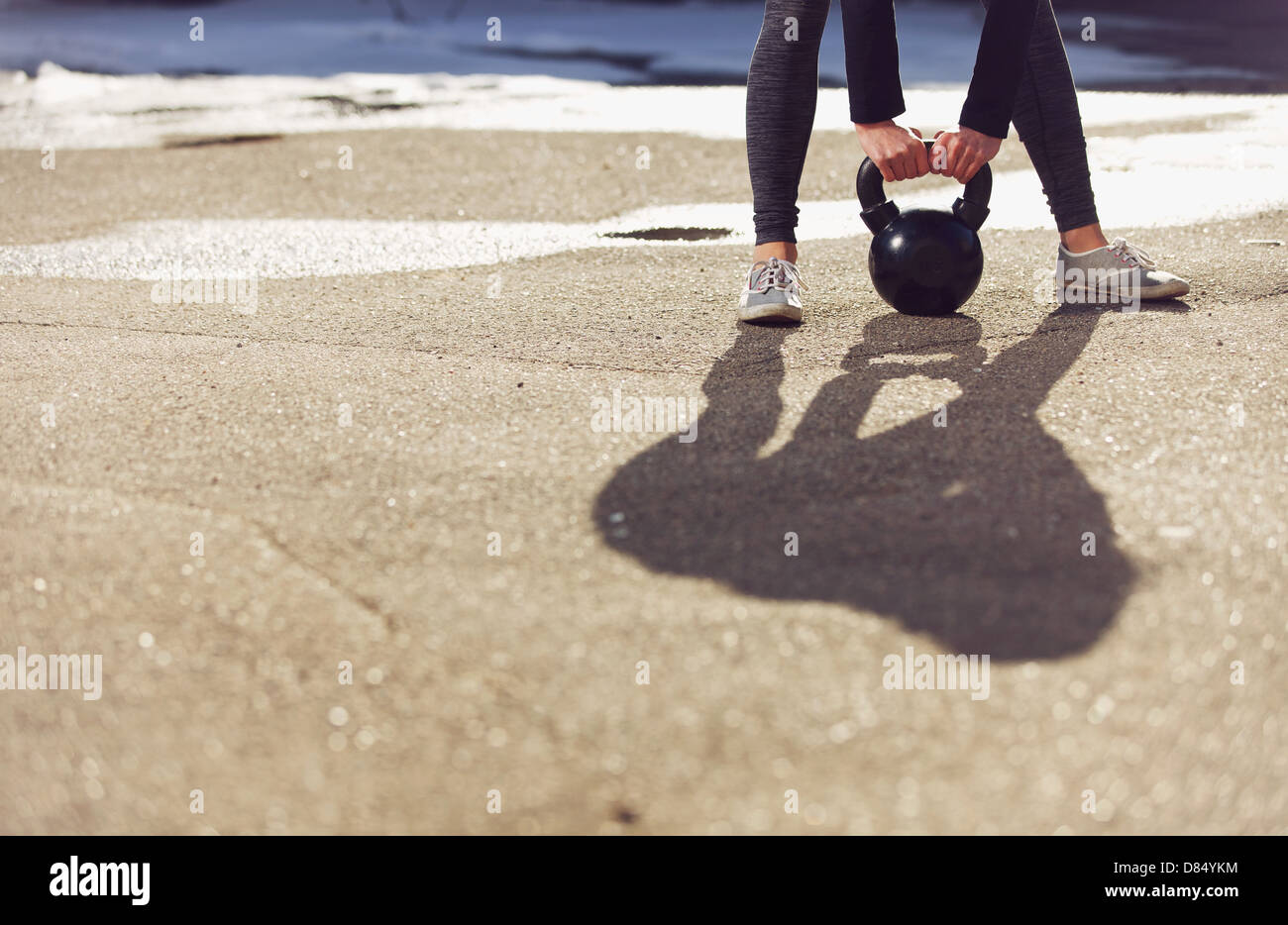 Shadow of a fitness crossfit woman lifting a kettlebell - Stock Image