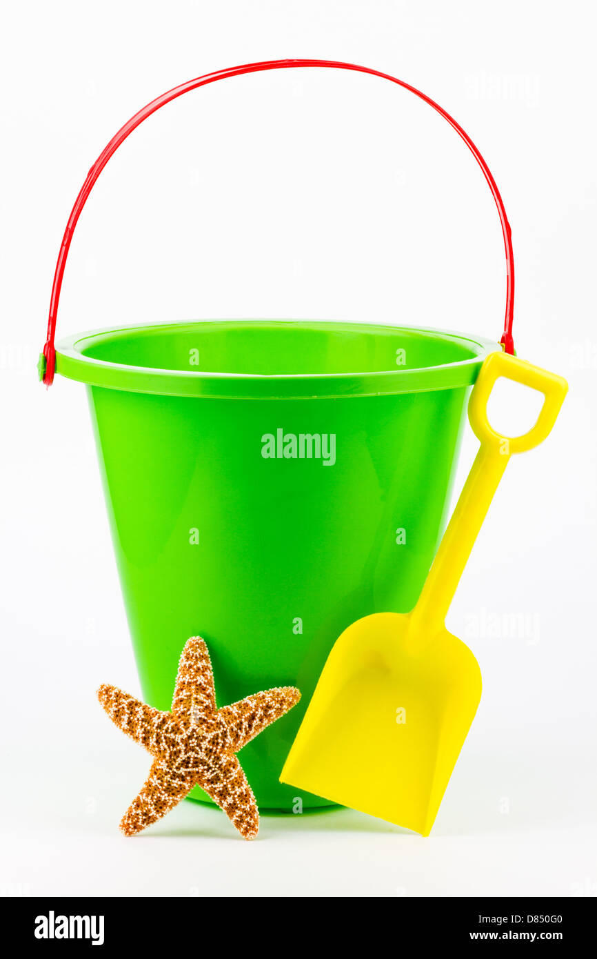 A green sand bucket with a yellow shovel and a starfish. - Stock Image