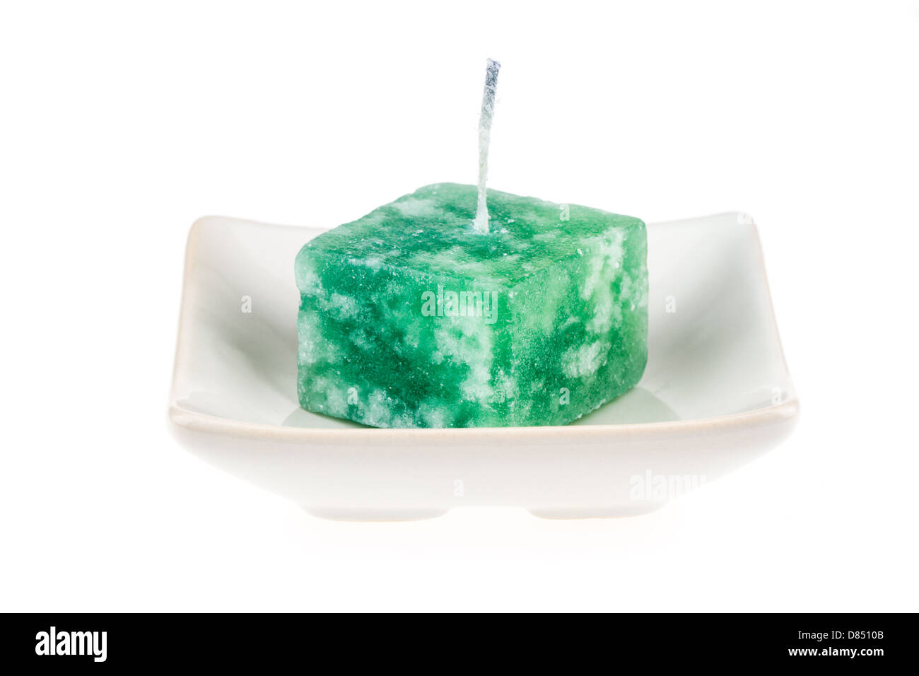 Green candle on a plate isolated on a white background. - Stock Image