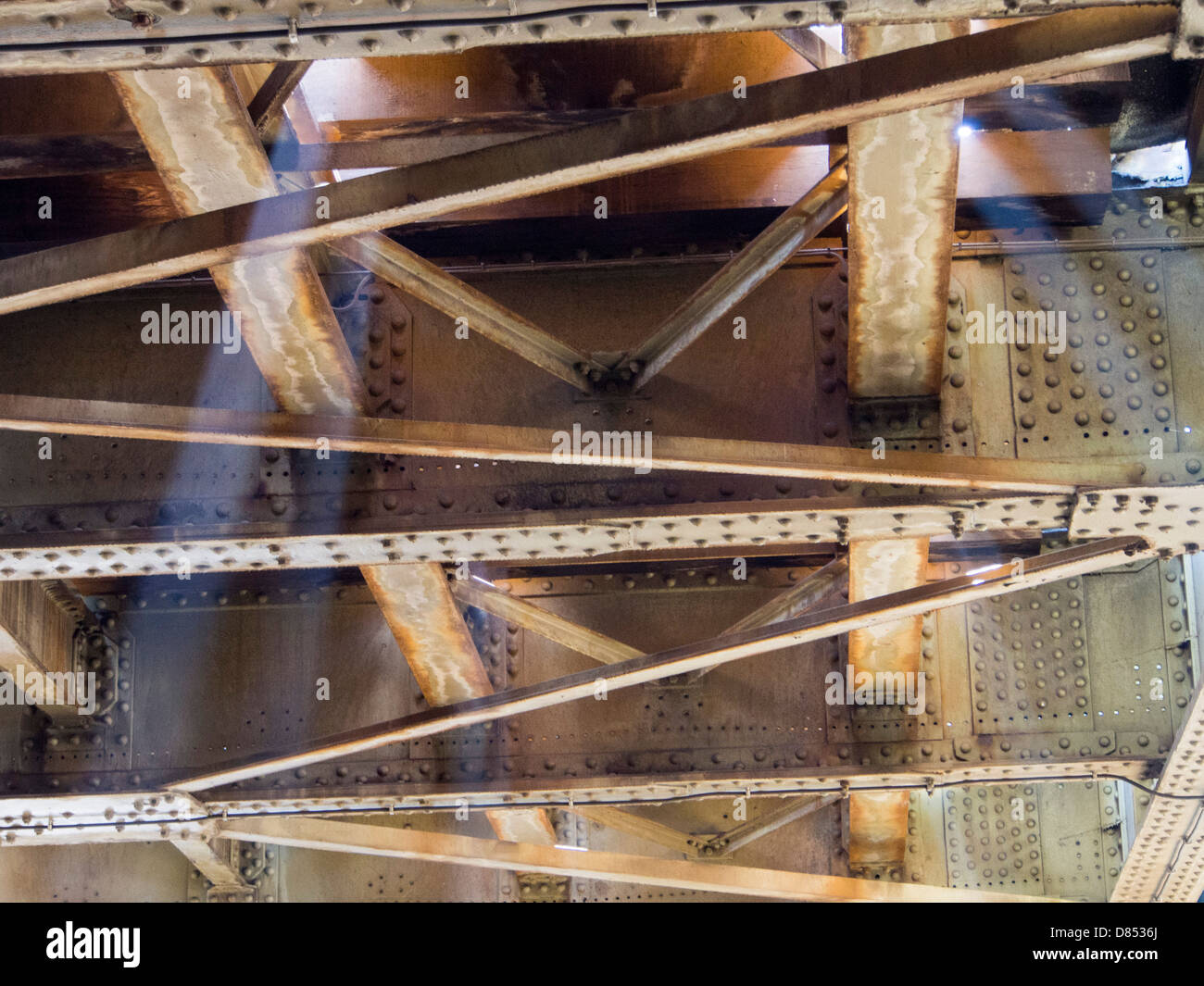 Shafts of light below railway tracks on a bridge in Amsterdam, Netherlands. Stock Photo