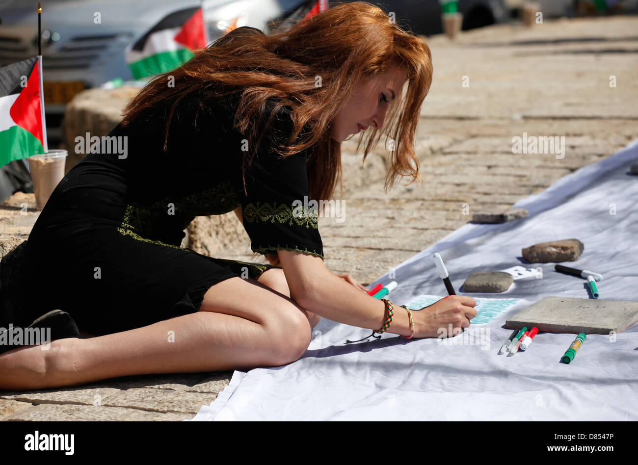 Young Israeli Arab student drawing the Palestinian flag before a pro Palestinian demonstration in Jaffa Israel - Stock Image