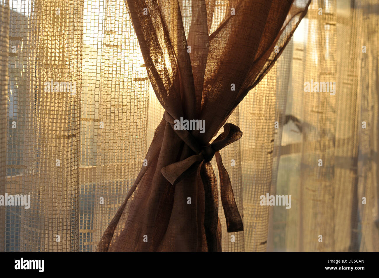 Net curtains tied back in a South African home. - Stock Image