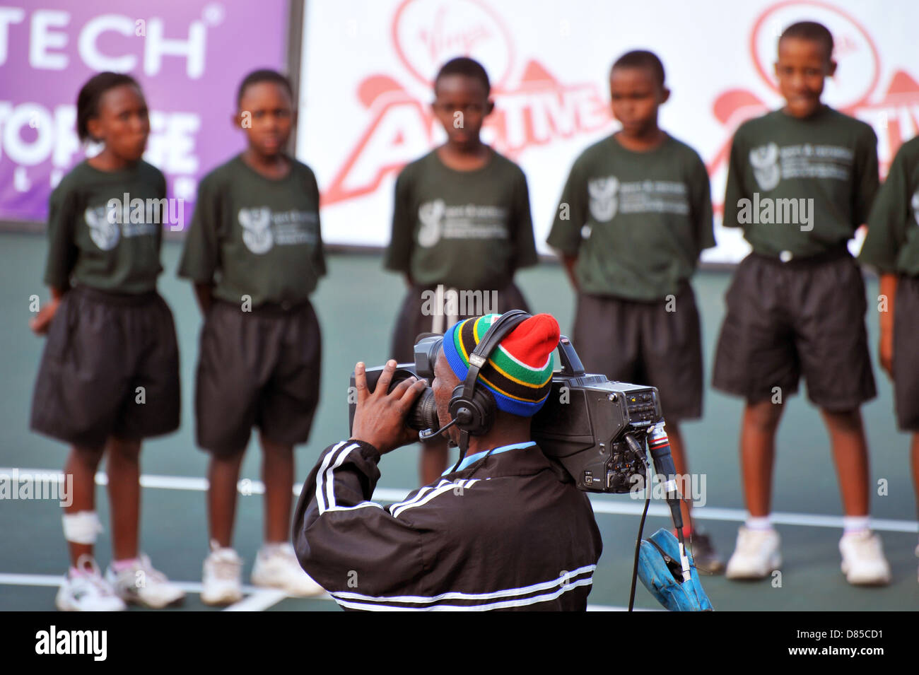 A cameraman wearing a South African flag hat filming at the 2013 Soweto Open Tennis Tournament. - Stock Image