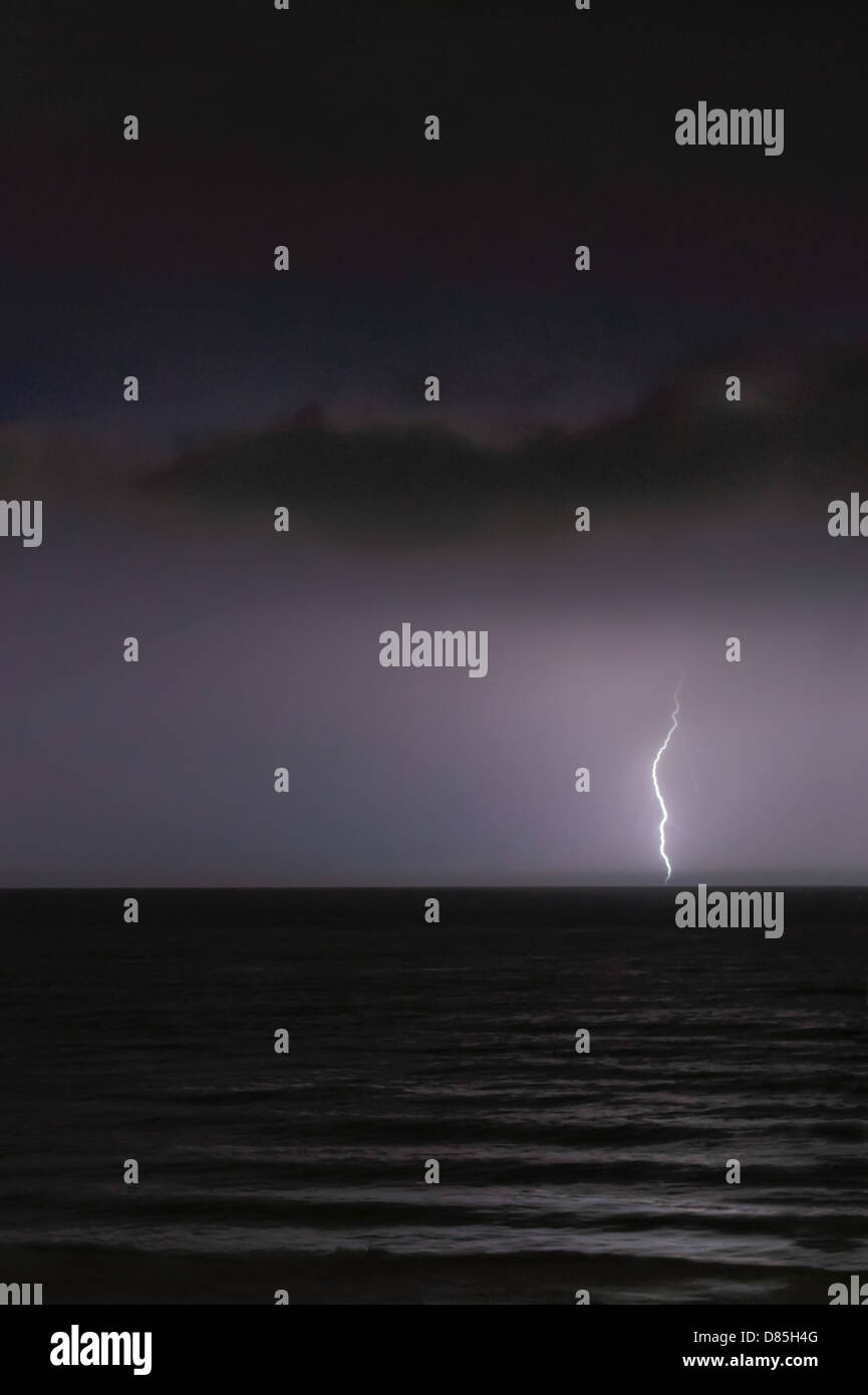Lightning bolt in distance over the sea at night - Stock Image