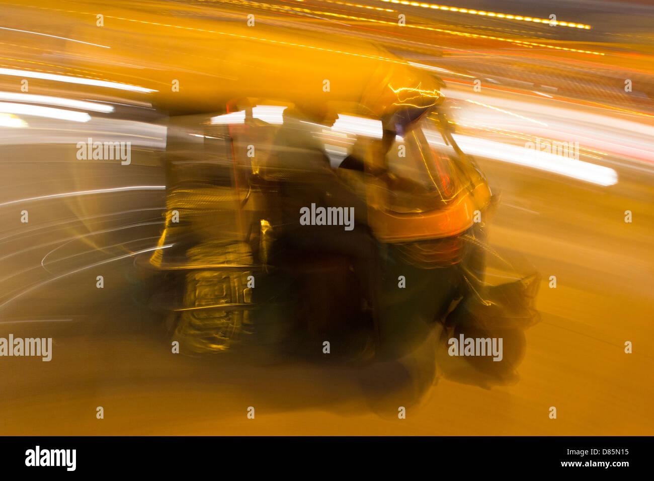India, Uttar Pradesh, New Delhi, Rickshaw and traffic at night with blurred motion effect - Stock Image