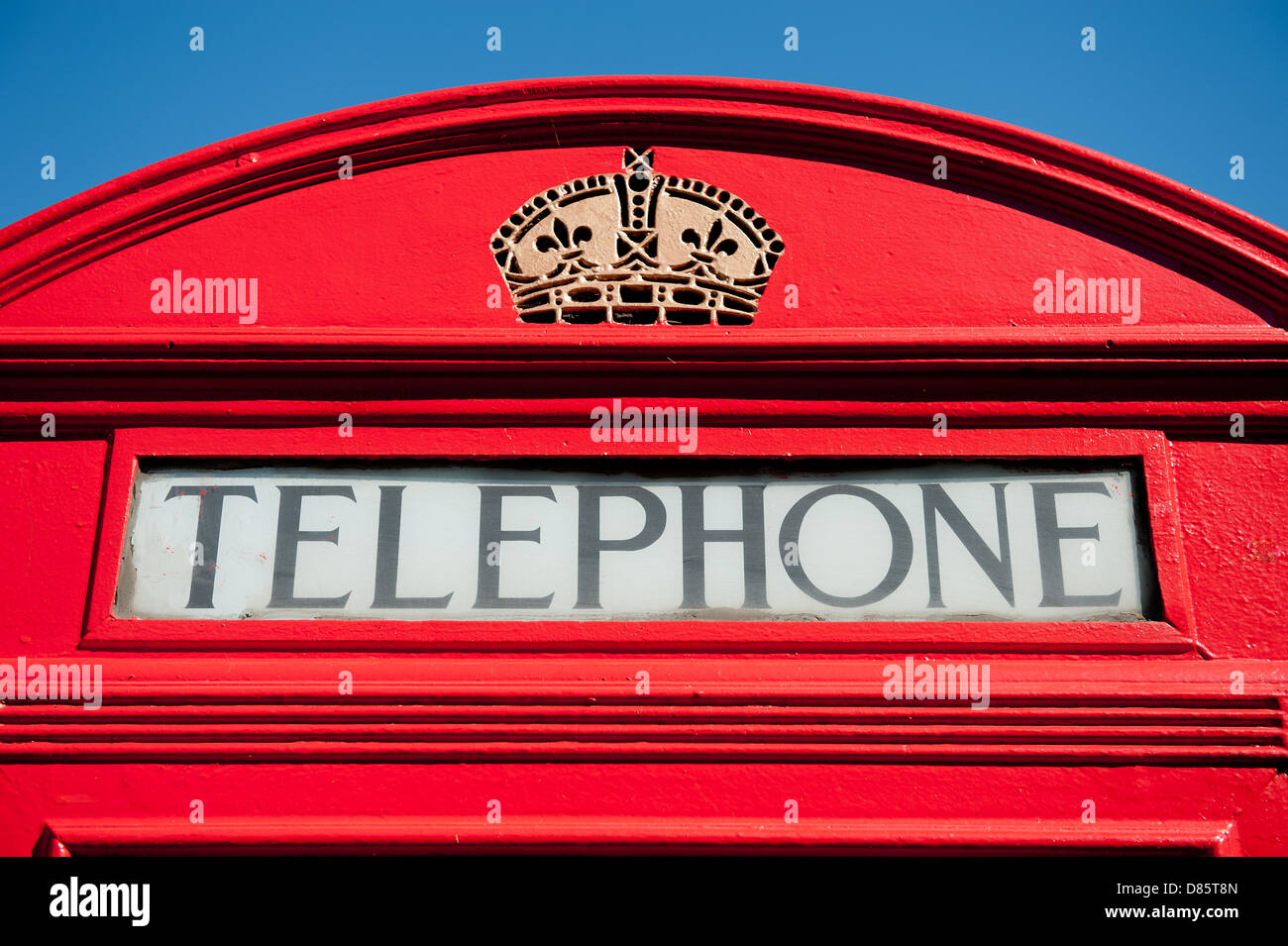 Old style red British telephone box against a clear blue sky Stock