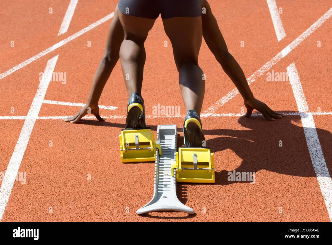 Dark-skinned sprinter in start position prepares for the start - Stock Image