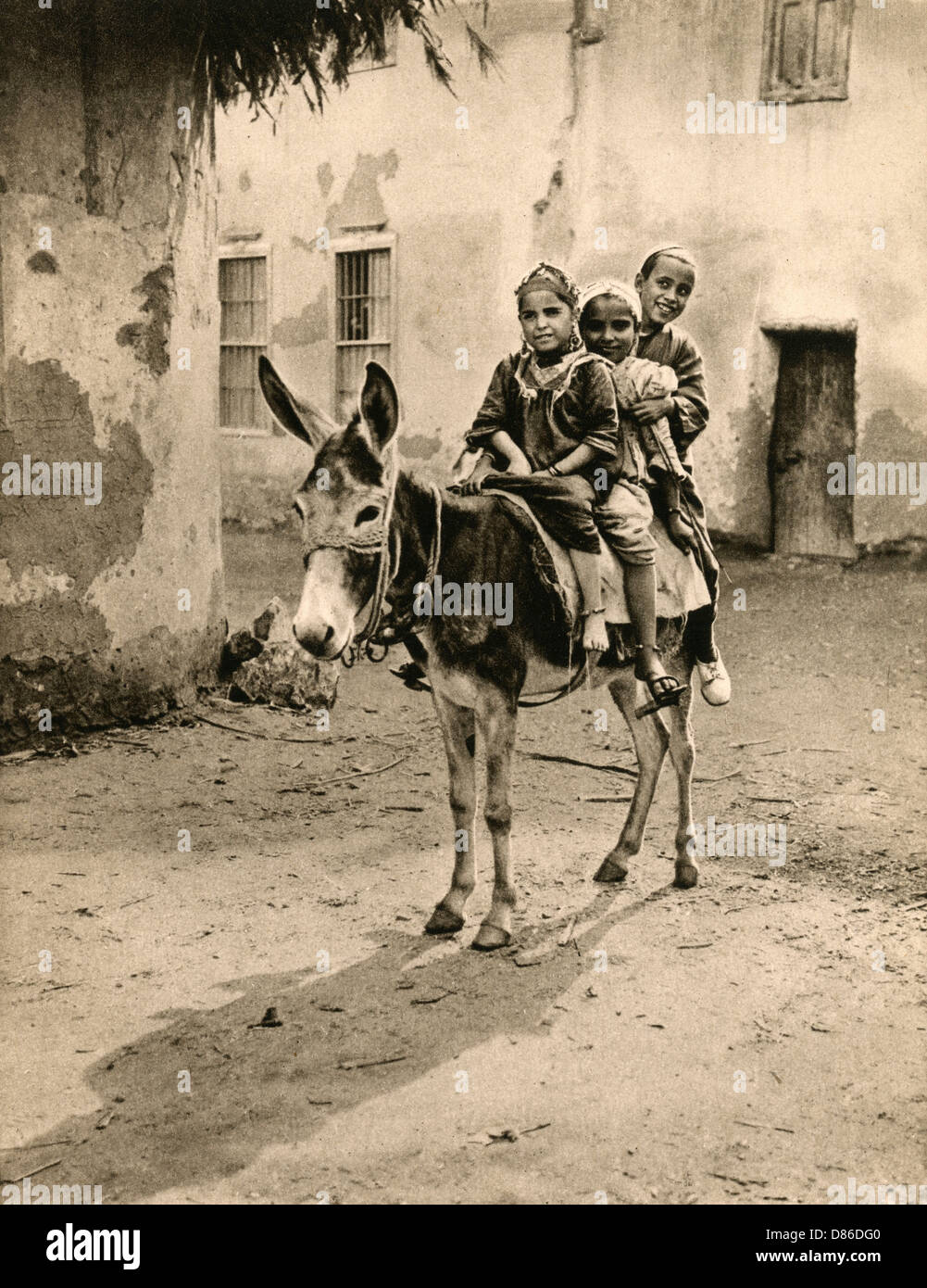 Children At The Village Of Marg Near Cairo Riding A Donkey - Stock Image
