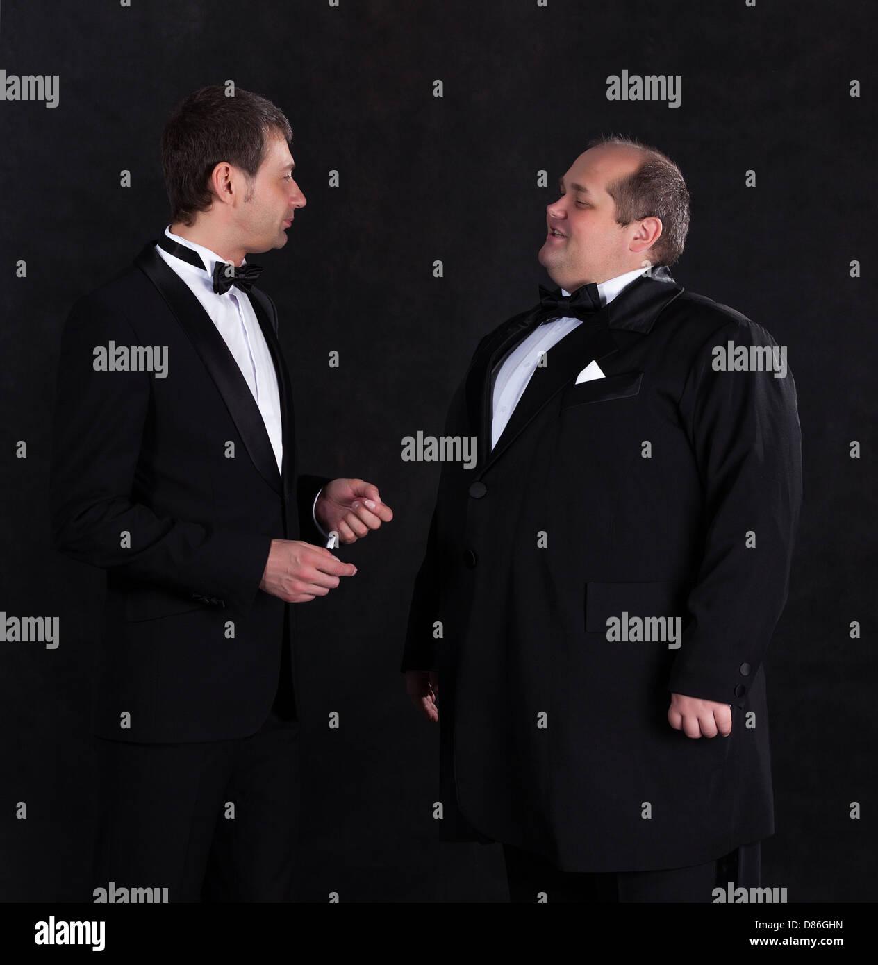 Two stylish businessman in tuxedos, on black background - Stock Image