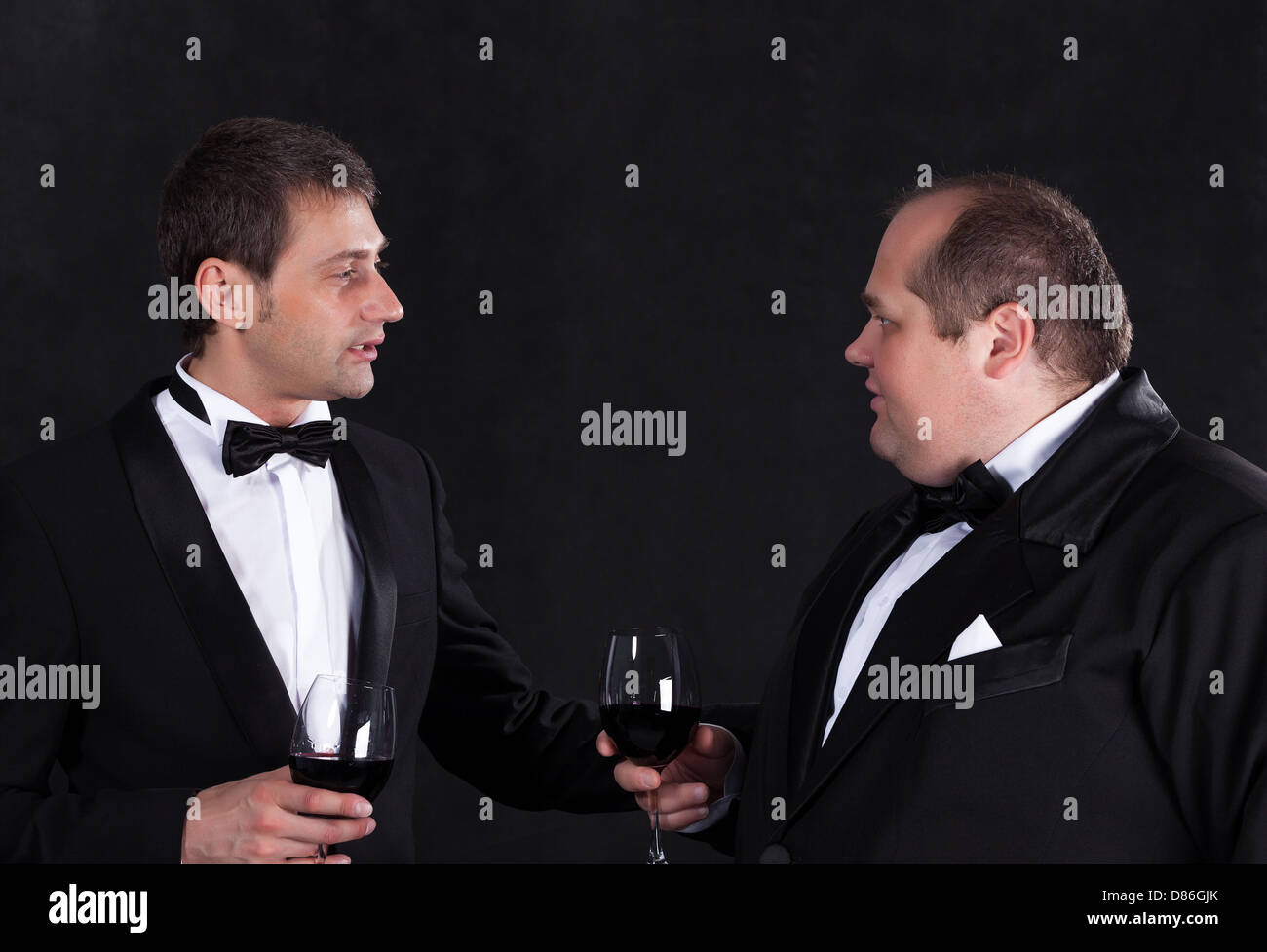 Two stylish businessman in tuxedos with glasses of red wine, on black background - Stock Image