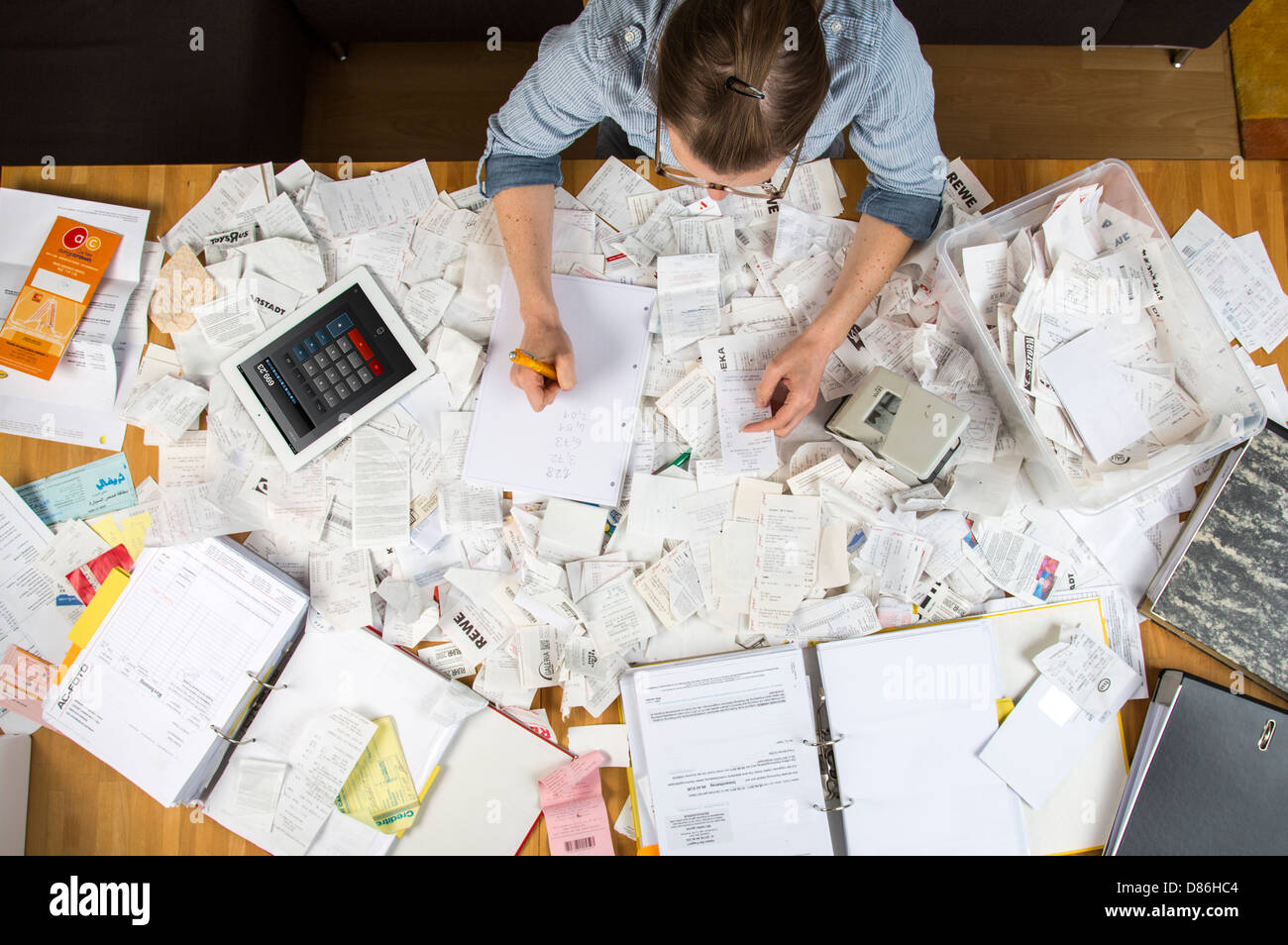 Young woman is sitting at home and sort out bills, receipts and other papers for her tax declaration. - Stock Image