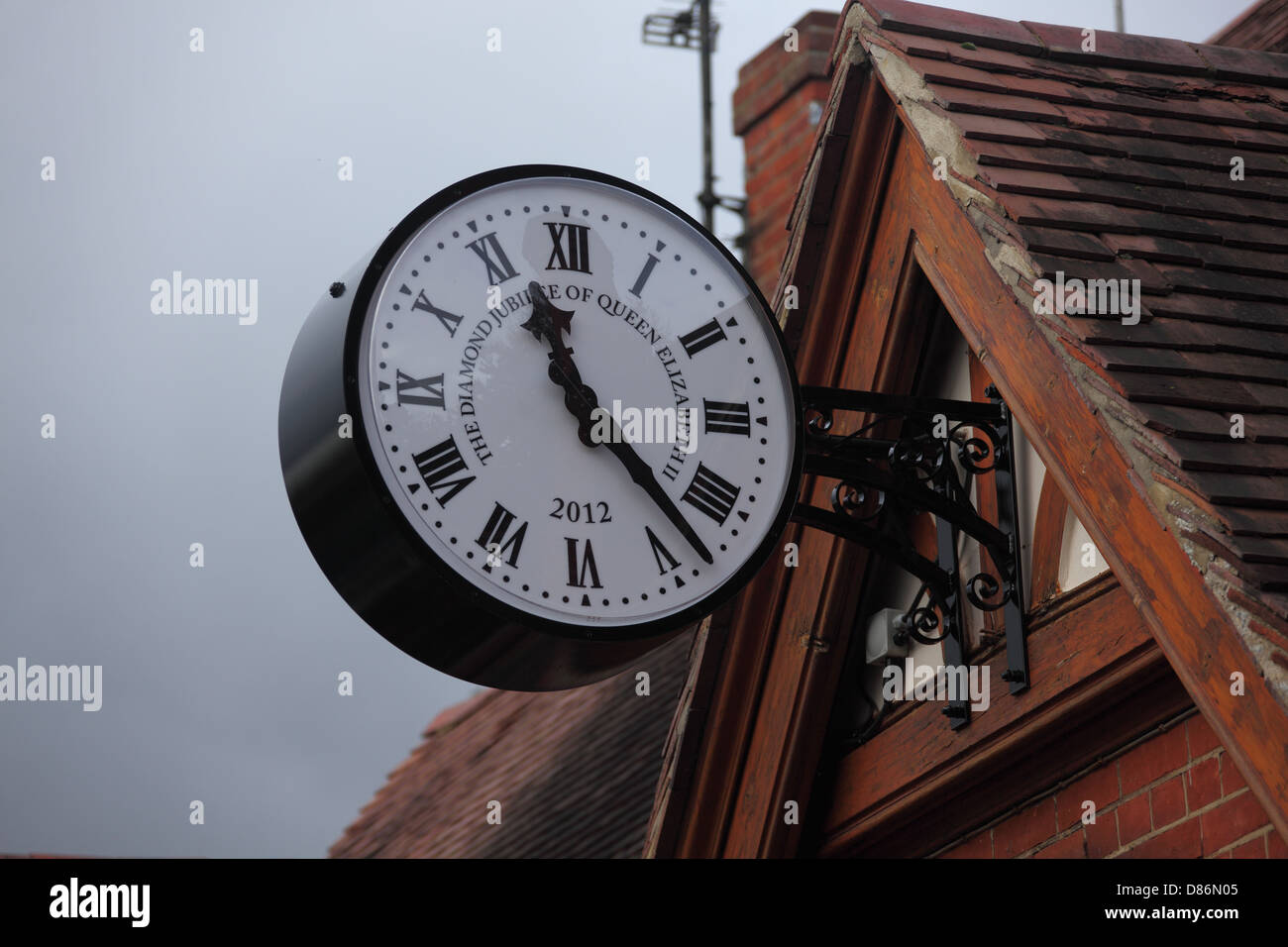 Small village commemorative clock on the village hall to commemorate the Queens Diamond Jubilee. - Stock Image