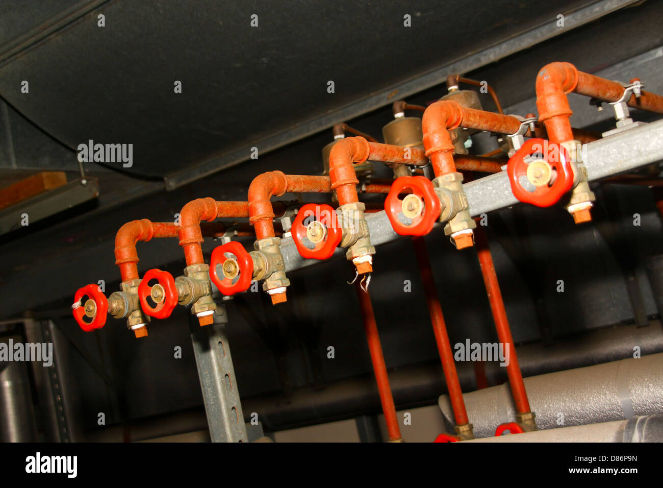 pipe manifold in plant room with stopcocks Stock Photo
