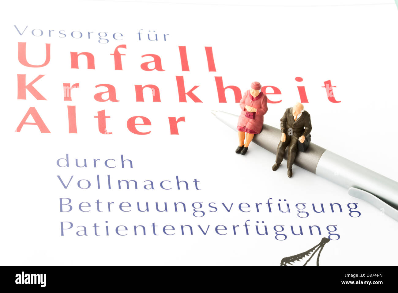 Figurines sitting on pen with advance directive form, close up Stock ...