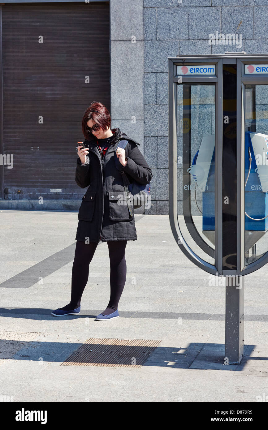 Young woman checks her mobile phone while standing beside a public telephone. O'Connell Street, Dublin, Republic - Stock Image