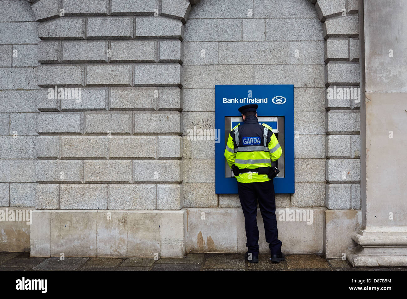 Member of the Garda (Irish police force) using an ATM at the bank of Ireland  during a recession. College Green, - Stock Image
