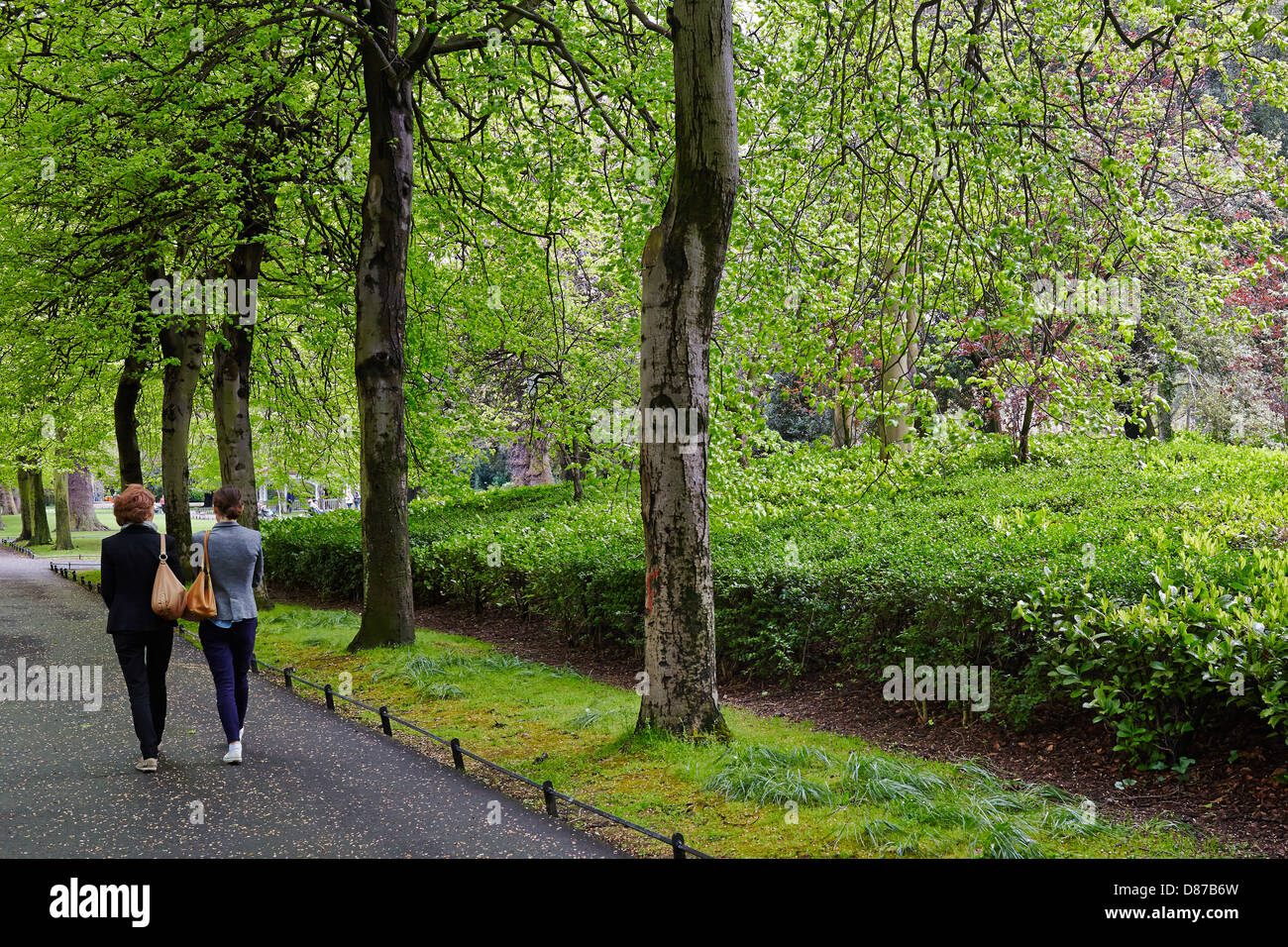 Two young people walk through the grounds of Saint Stephen's Green, Dublin, Republic of Ireland - Stock Image