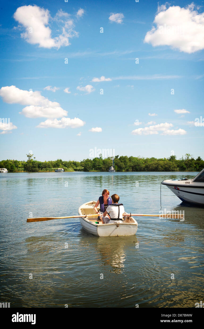 Two young people take a rowing boat out on the Norfolk Broads during a hot summers day Stock Photo