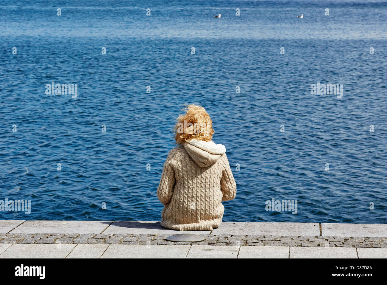 A young woman sits in the sunshine on Grand Canal  Harbour in Dublin's dockland area - Stock Image