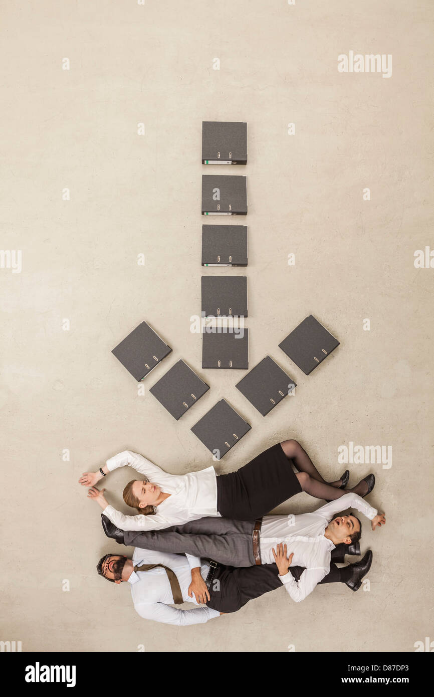 Business people lying below down arrow sign formed by files - Stock Image