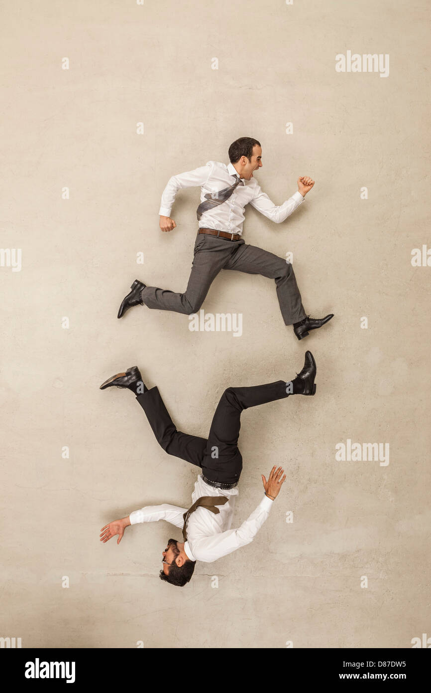 Businessmen chasing in opposite direction - Stock Image