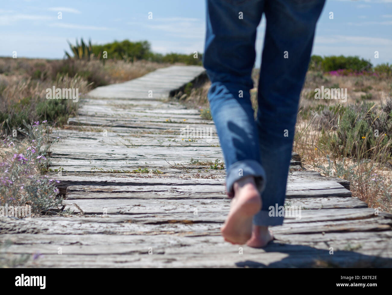 A woman walks barefoot on a wooden gangway in a desert island on a sunny day - Stock Image